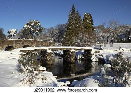 Stock Photo of England, Devon, Postbridge. Snow covered clapper.