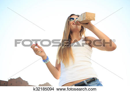 Stock Photo of girl drinking from a paper bag in the street.
