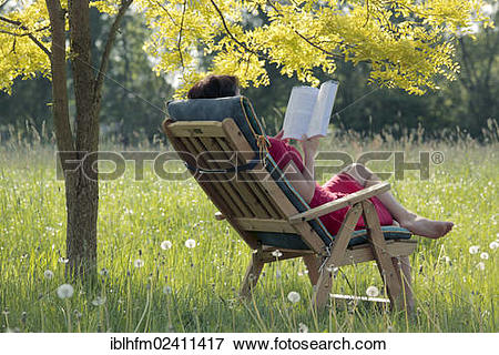 """Picture of """"Young woman sitting and reading a book in a garden."""