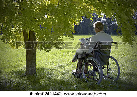 """Stock Photo of """"Elderly man sitting and reading a book in a."""