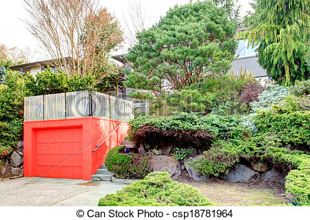 Stock Image of Clapboard siding house on a hill. Red door garage.