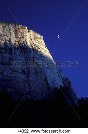 Stock Photo of Mountain cliff with deep blue sky and quarter moon.