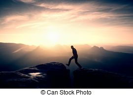 Stock Photography of Crazy hiker umping between rocks. Marvelous.