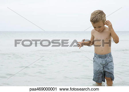 Stock Photography of Little boy standing knee deep in ocean.