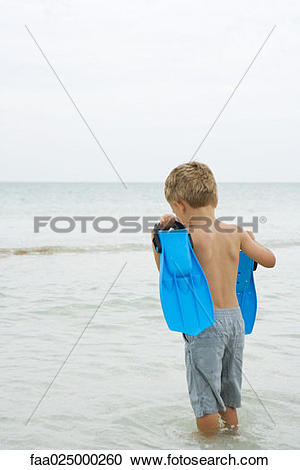 Stock Photography of Young boy standing knee deep in water.