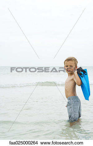Stock Photo of Young boy standing knee deep in water, carrying.