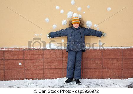 Stock Photo of boy kid is standing near wall with snowballs snow.