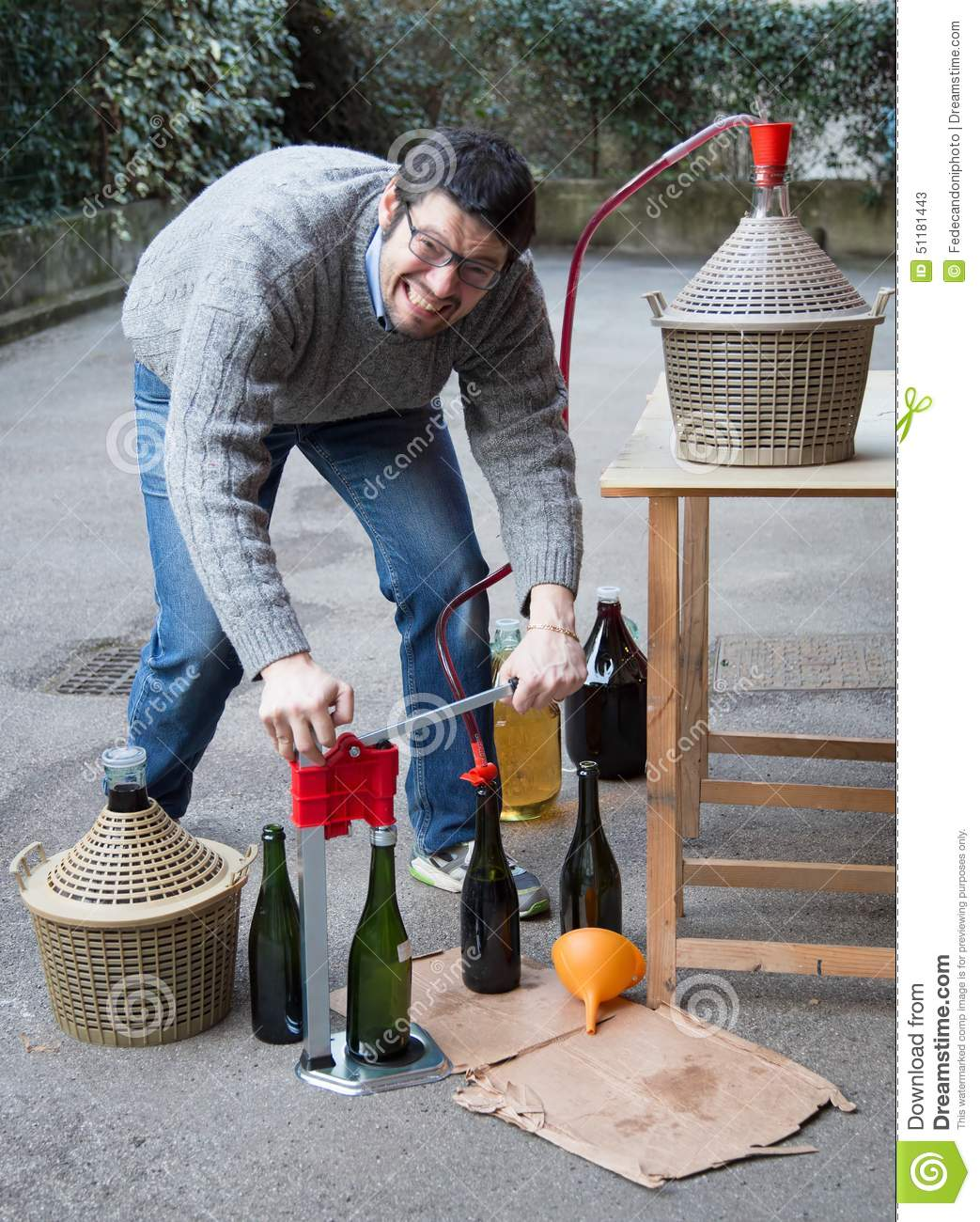 Man White Bottling Red Wine From The Demijohn Stock Photo.