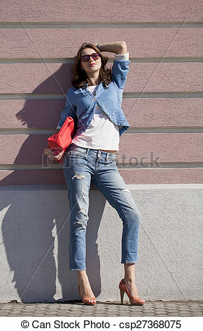 Picture of Beautiful woman body in denim jeans on wall background.