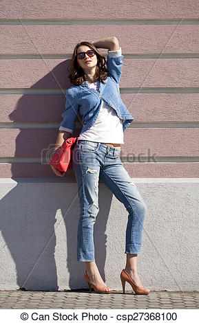 Stock Photography of Beautiful woman body in denim jeans on wall.