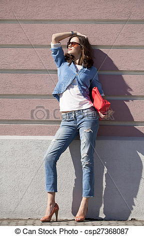 Pictures of Beautiful woman body in denim jeans on wall background.