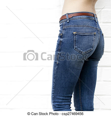 Stock Images of Beautiful woman body in denim jeans on white brick.