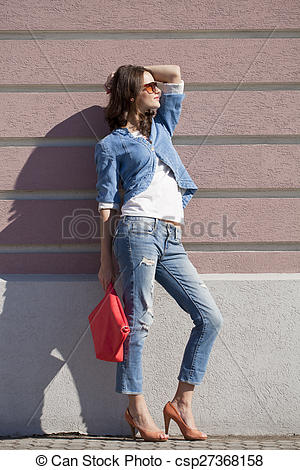 Stock Images of Beautiful woman body in denim jeans on wall.