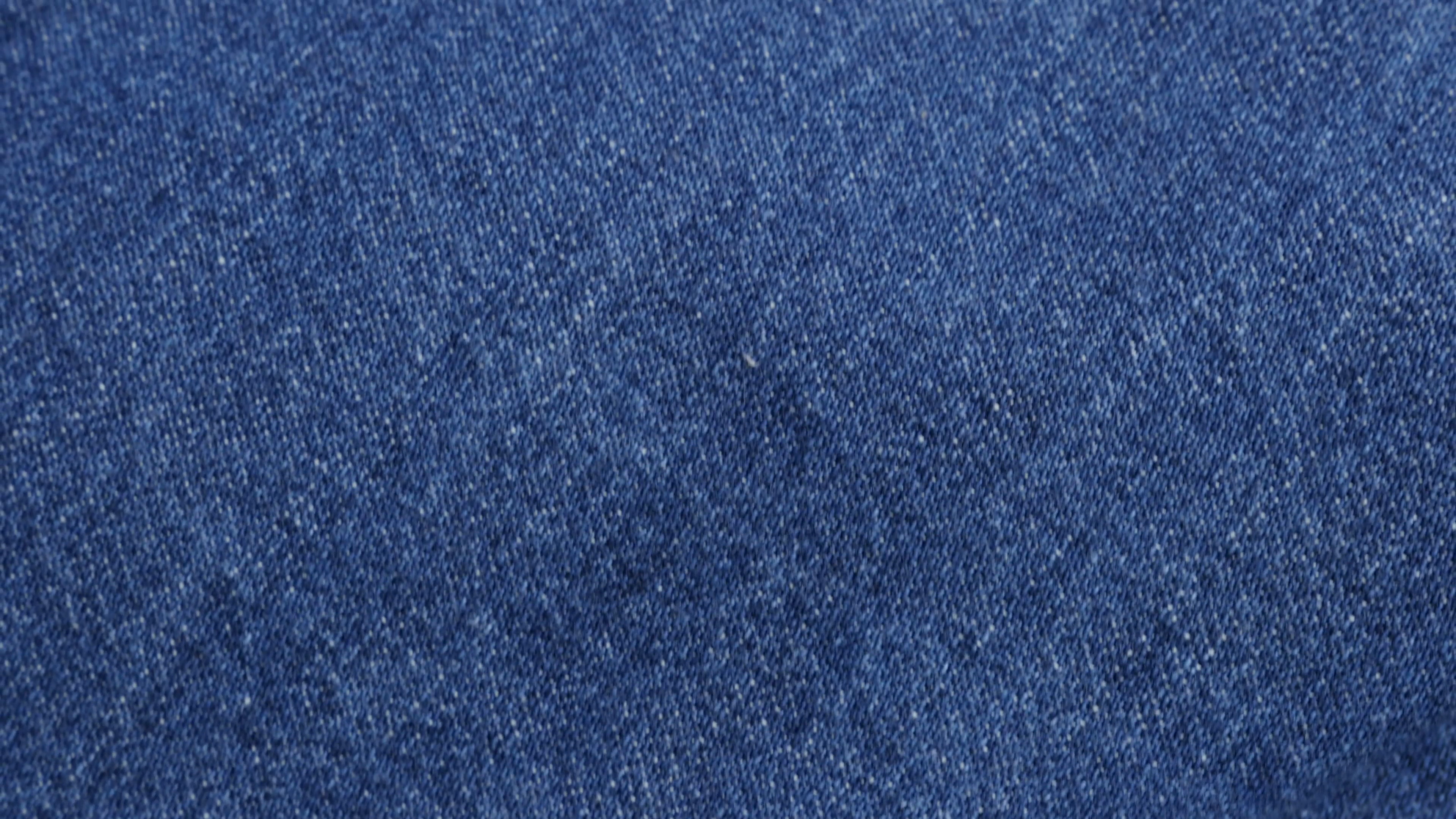 Clothing fabric of blue high quality denim details and texture tilting 4K  2160p 30fps UltraHD video.