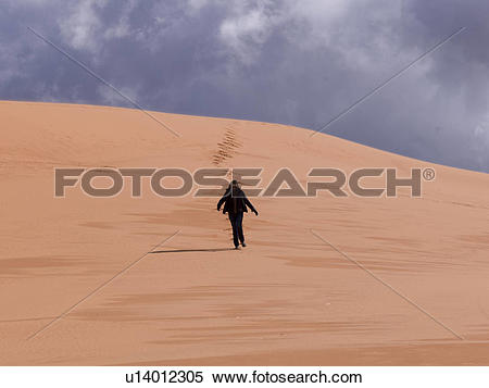 Stock Image of Person walking in a desert, Coral Pink Sand Dunes.