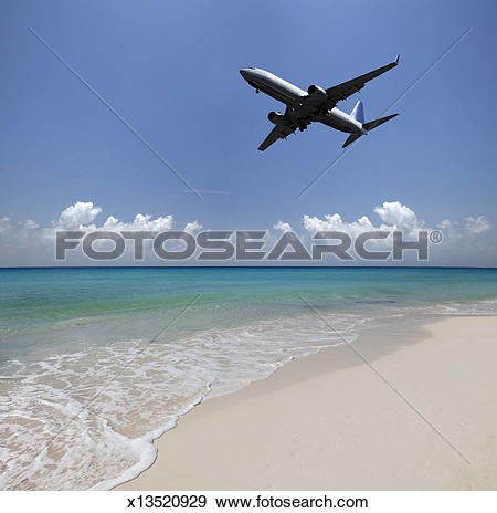 Stock Photograph of Airplane flying over a deserted beach.