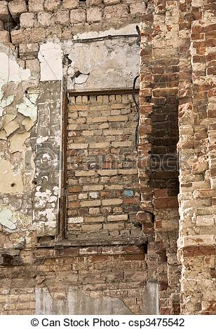 Stock Photo of Pledged window in an old brick wall. Destruction of.