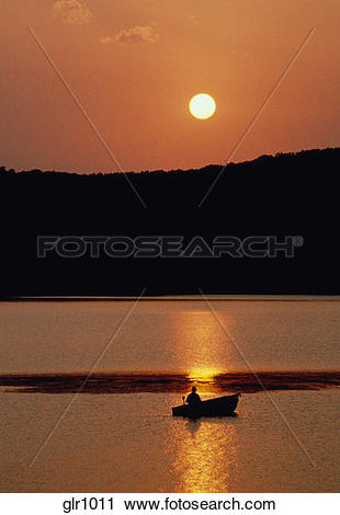 Stock Photography of Silhouette of man fishing from boat at sunset.