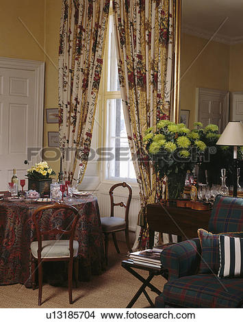 Stock Photo of Red+cream patterned curtains in dining room with.