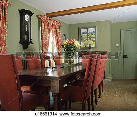 Stock Photo of Upholstered red chairs and rectangular oak table in.