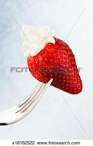 Stock Photo of Strawberry dipped in whipped cream on fork.