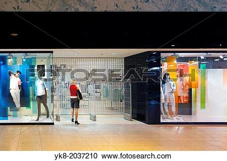 Stock Photography of Woman standing at closed shop gate.