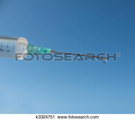 Stock Photography of Disposable syringe against the blue sky.