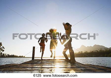 Stock Image of Family, in swimwear, running along jetty, jumping.