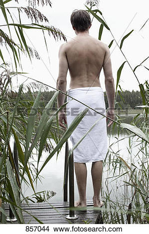 Stock Photo of A man standing on a spa jetty staring off into the.