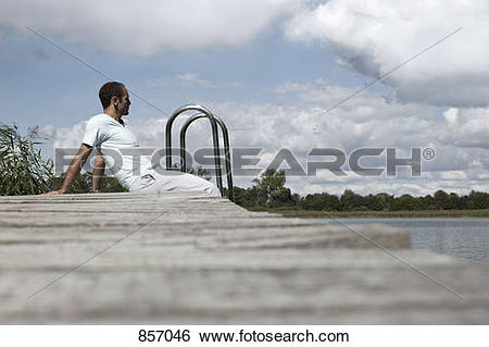 Stock Images of A man sitting on a spa jetty staring off into the.