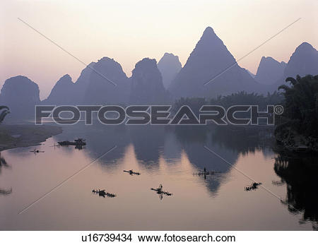 Stock Photo of Fishermen on boat and distant mountain.