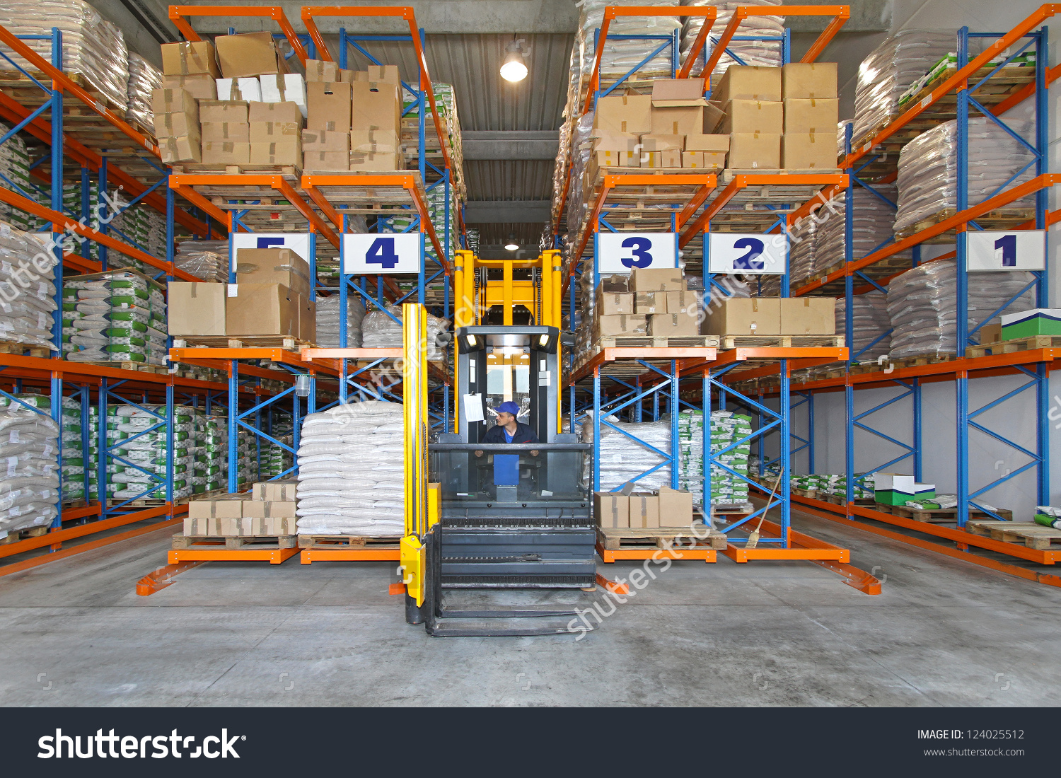 Distribution Warehouse With High Rack Stacker Forklift Stock Photo.