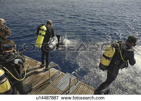 Picture of Divers entering water from back of dive boat VIP ONE.