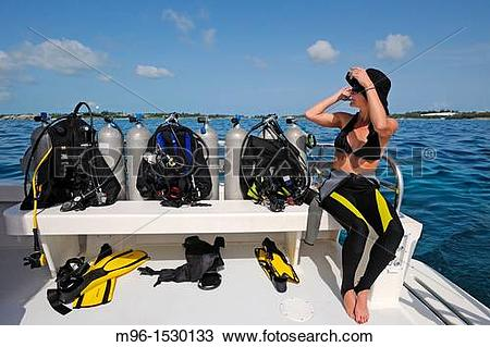 Stock Photo of Female diver sits next to air tanks on dive boat.