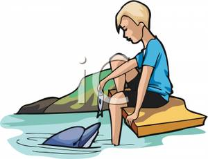 Child Sitting On A Dock Feeding A Dolphin.