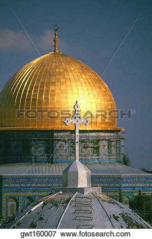 Picture of Cross on the dome of a church with a mosque in the.