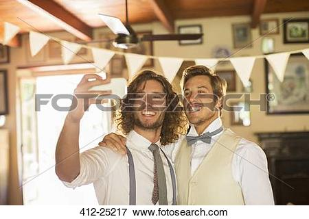 Picture of Bridegroom and best man photographing self in domestic.