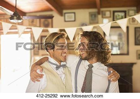 Stock Photo of Bridegroom and best man embracing in domestic room.