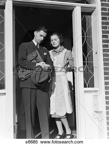 Stock Image of 1930S Husband Wife Stand In Open Door Man Going To.