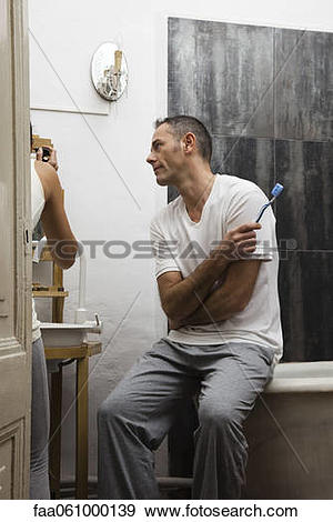 Stock Photograph of Husband waiting in bathroom while wife applies.