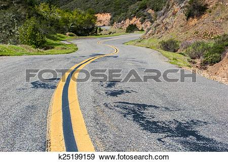 Stock Photograph of Double yellow line down windy mountain road.