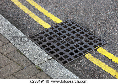 Stock Photography of Street drain over Double yellow line on.