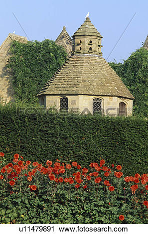 Stock Photography of Clipped hedge in front of stone dovecot in.