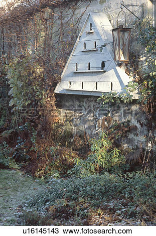 Stock Photo of Antique dovecote and lantern on old stone wall in.