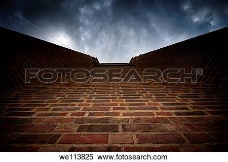 Stock Image of Brick wall leading to dramatically looking dark sky.