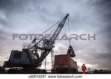 Picture of Low angle view of crane loading truck under dramatic.