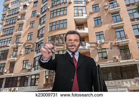 Stock Photography of adult man holding key to dream house with.