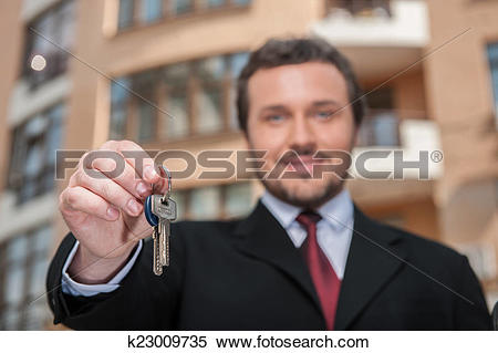Stock Image of closeup on adult man holding key to dream house.