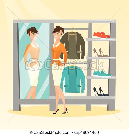 Caucasian woman trying on jacket in dressing room.