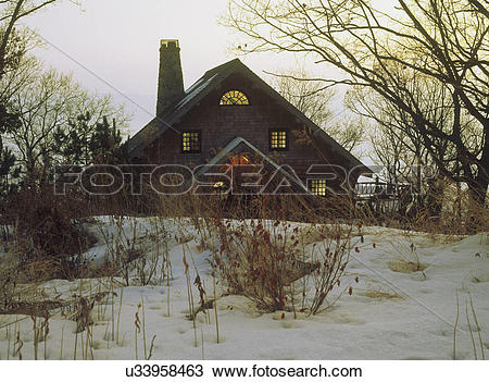 Stock Photo of EXTERIOR: Log home in snow, twilight, trees, dried.